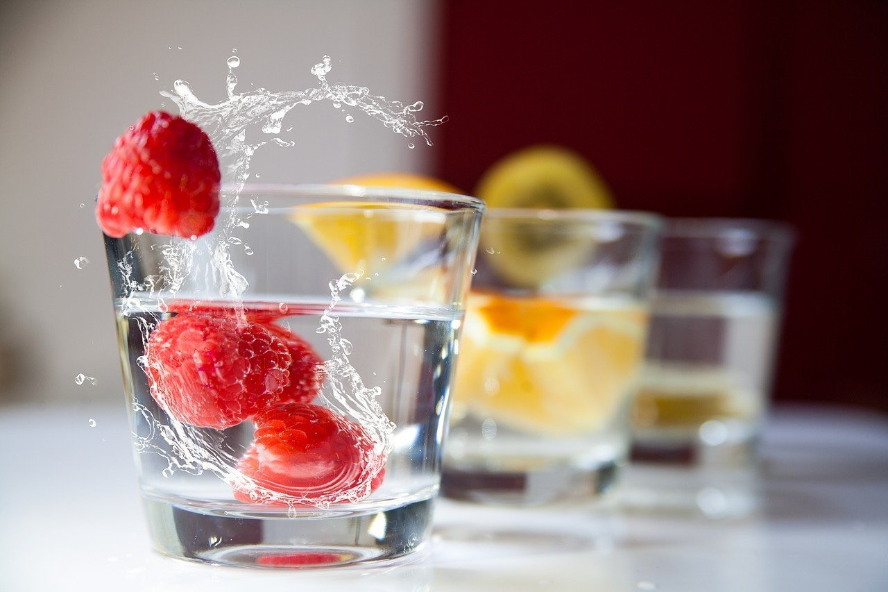 Photo of glasses on water with fruit in them