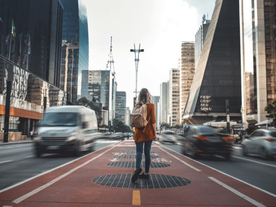 Image of girl walking down sidewalk with traffic on both sides