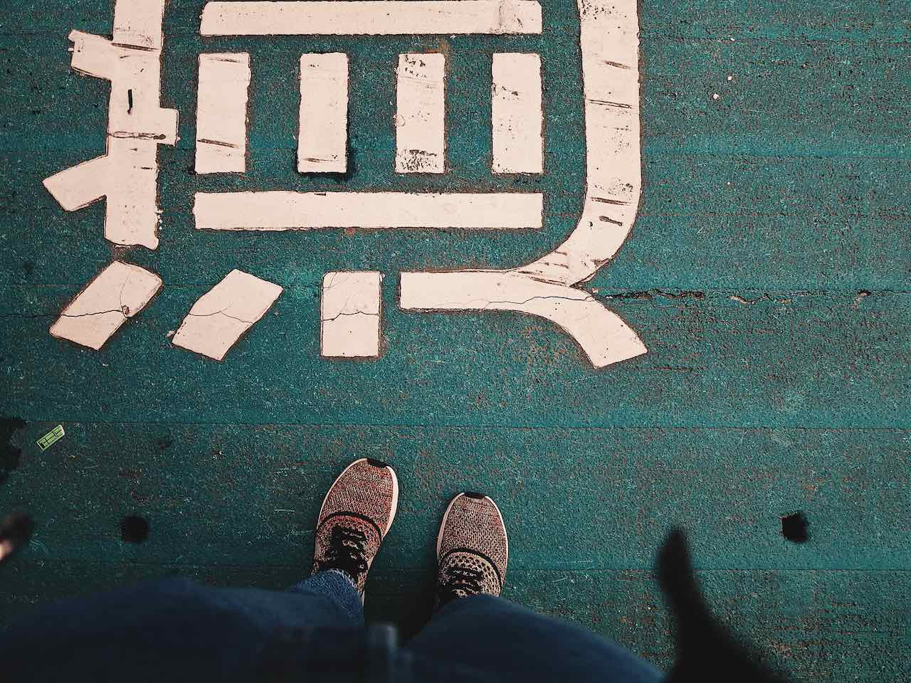 Image of feet and mandarin writing on a road