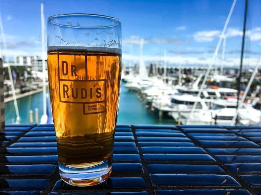 Image of a glass of beer sitting on the waterfront deck of Dr Rudi's | Image © ExpatAlli.com