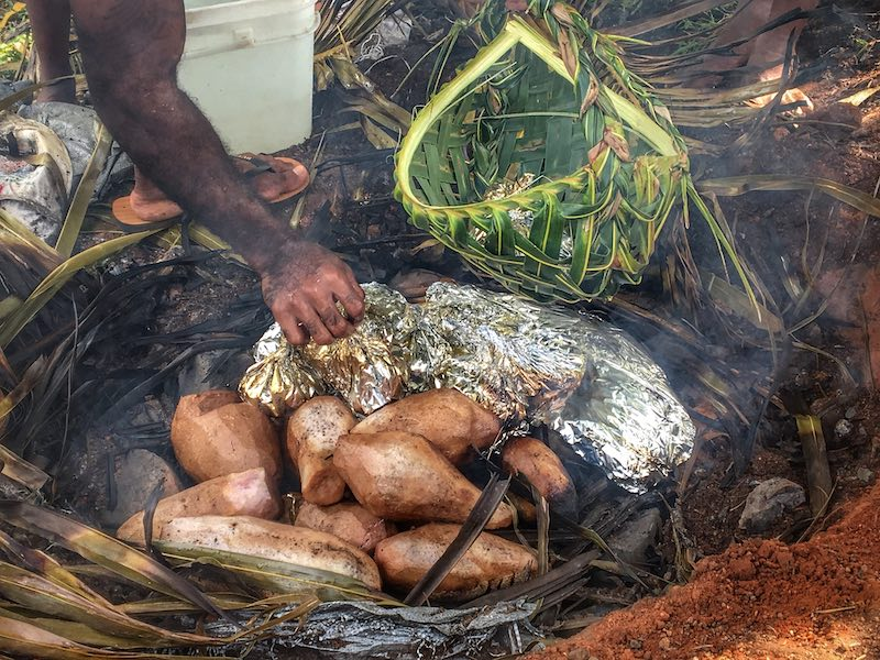 Image of Fijians putting food into a palm basket during a lovo | Image © ExpatAlli.com