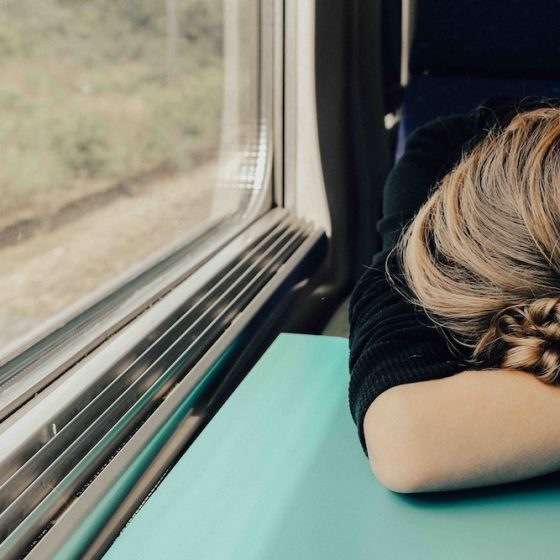 Girl on train with her head on table
